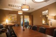 The main conference room at Hilliard Lyons Olympia Park office features a modern mirror and chandeliers, textured flooring, and artwork on the walls.