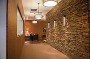 A hallway lined with layered stone leads visitors into the offices of MKCC Group, a wealth advising group for Hilliard Lyons.