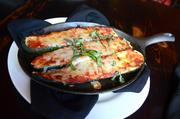 The grilled zucchini pizzola is served in a sizzling skillet with a generous helping of mozzarella and tomato sauce.