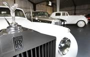 The 1962 Silver Cloud's hood ornament and front grill are shown, with other cars kept in the company's Seattle garage.