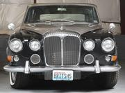 The silver-black 1969 Daimler-Jaguar DS420 limousine owned by Roy Dubrow and British Motor Coach company is stored in the company's fleet garage.