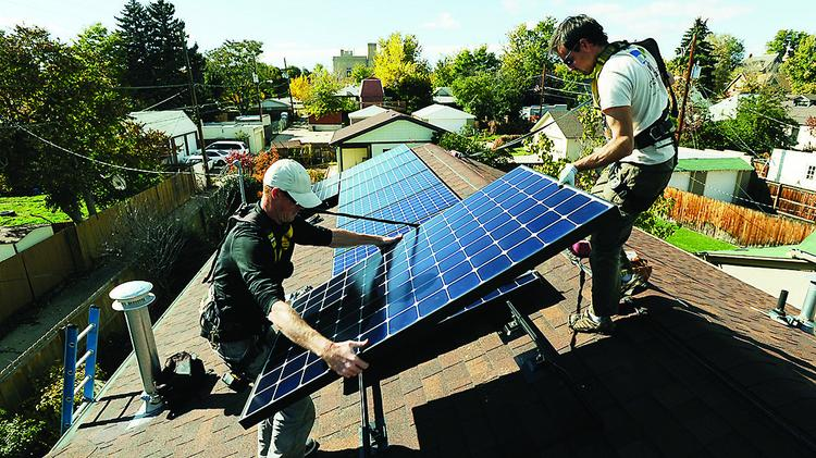Workers put solar panels on a house near 35th and Decatur in Denver.