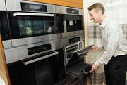 Doug Shanefield, sales manager with Coldwell Banker Pacific Properties, examines a Miele oven that retails for about $3,000, which will also be standard.