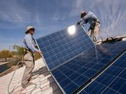 Jacob Moore and Eliel Ortega, installers with Sun Valley Solar Solutions, work on a residential rooftop solar system in Gilbert.