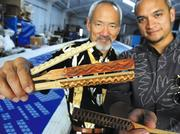 Sig Zane and his son, Kuhao, show their design tools — bamboo stamps known as ohe kapala in Hawaiian.Their designs are printed on kapa cloth made from the bark of the wauke tree.