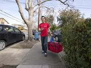 Food in hand, Tony Xu of DoorDash heads toward the delivery destination.