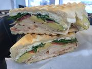 Super Food Truck's turkey pesto panini, which features turkey, prosciutto, avocado, spinach with tomato and goat cheese on a French baguette.