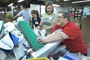 Helen Schrock, red shirt, grabbed a pile of donated medical supplies that started sliding.  She and Michelle Jutt, left, and Tammy McDill, far left, were among the KentuckyOne Health employees going through the pile to determine if any of the supplies were past the noted expiration dates.