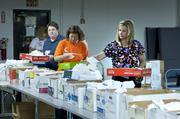 Kimberly Hobson, right, Petie Anderson, center, and Theresa Kirk filled a line of boxes with donated medical supplies.