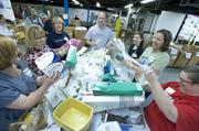 Pictured from left to right: Jill McClain, Shirley Miller, Vicki Basham, Rob Murphy, Tammy McDill, Michelle Jutt and Helen Schrock dug into a pile of donated medical supplies to determine expiration dates of the supplies.