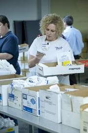 Sherry Boggs read a package as she distributed medical supplies in boxes for storage.