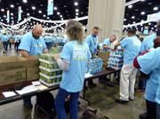 Kroger Co. employees attending a leadership summit helped pack food boxes for Dare to Care Food Bank.