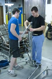 David Carroll, left, and Will Stewart assembled a patient sling lift with the parts from two that weren't functioning properly.