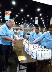 The Kroger volunteers pack donated cleaning products into boxes of household supplies during a Give A Day week of service event held at the Kentucky Exposition Center.