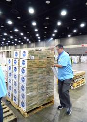 A Kroger volunteer wrapped stacked boxes so they can be transported.