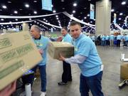 Jason Sowder of Cincinnati received a box from Kavin Haynes, left, of Castlerock, Colo., as their assembly line finished packing boxes.