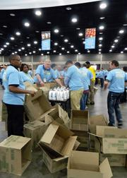 Kroger volunteers prepare to pack empty boxes at the beginning of one of the many assembly lines at the Kentucky Exposition Center during a Give A Day service project to benefit Dare to Care Food Bank.
