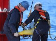 Crew members lower the pinger locator into the ocean from the Australian ship Ocean Shield.