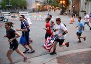 A runner holding a flag makes his way to the finish.