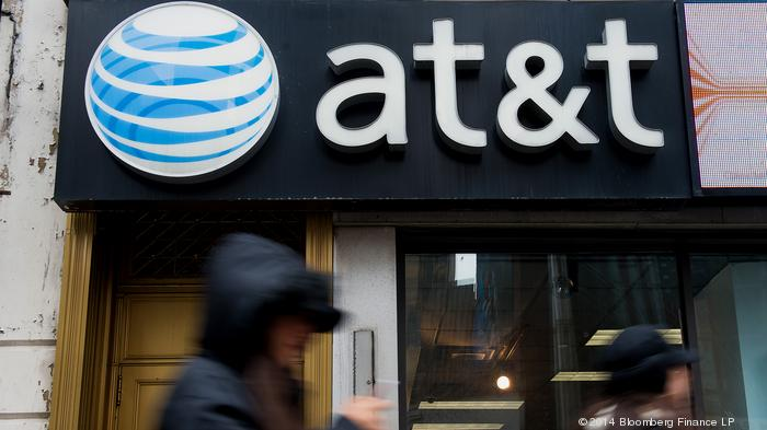Pedestrians walk past an AT&T Inc. store in New York, U.S., on Monday, Jan. 27, 2014. AT&T Inc. is scheduled to release earnings figures on Jan. 28. Photographer: Craig Warga/Bloomberg
