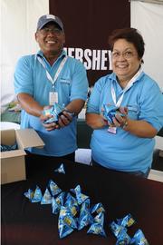 Stan and Norma Remata, volunteers for the LPGA LOTTE Championship,  serve spectators Maunaloa macadamia nuts.
