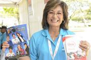Darcie Minami, volunteer for the LPGA LOTTE Championship, shows off the LPGA's 2013 fan book and program.