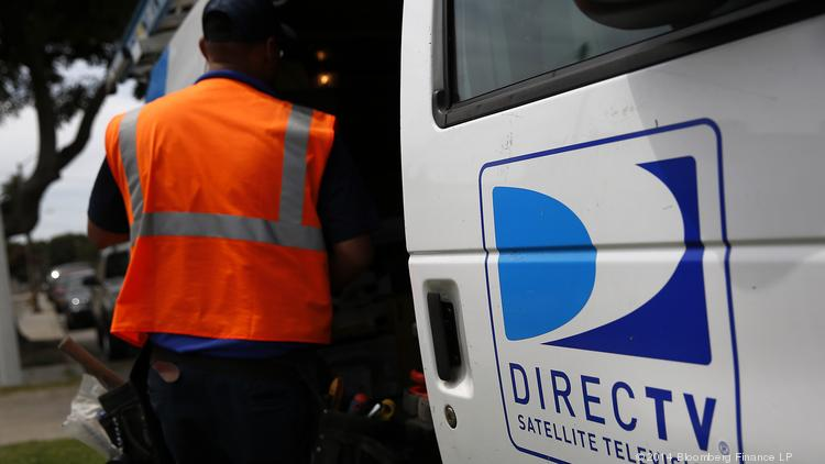 The DirecTV logo is seen as a technician stores equipment in a service truck after installing a new satellite TV dish at an apartment building in Lynwood, Calif.