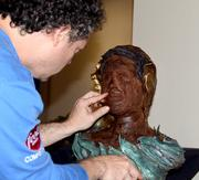 Sculptor Paul Joachim creates a portrait out of cake during the networking event.