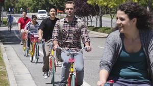 Googlers ride Google bikes through their Mountain View campus.
