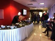Employees at evok advertising gather around the impressive food selection at a company party.