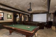The game room features a pool table and motorized drop-down movie screen.