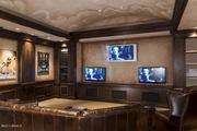 "A view inside the ""man cave,"" with televisions behind where the movie screen drops down."