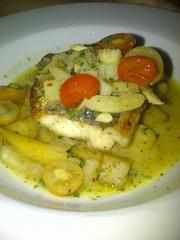 Branzino acqua pazza: pan-seared sea bass in a delicate sauce of white wine and garlic. It's served with teardrop tomatoes and winter veggies.