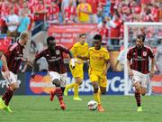Raheem Sterling of Liverpool competes with Michael Essien of AC Milan during the International Champions Cup 2014 match against Liverpool and AC Milan at Bank of America Stadium on August 2 in Charlotte.