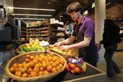 UW is catering to student demand for healthier food by stocking the dorms with kitchens, gourmet cafes and grocery stores such as District Market, where employee and UW student Elijah Keimig stocks fruit.