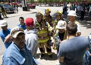 Dallas firefighters check with paint and drywall workers to make sure all personnel is accounted for.