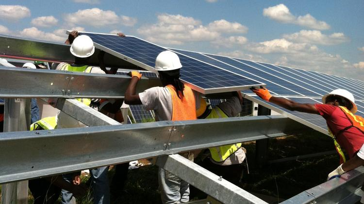 Crews for contractor Alpha Technologies install solar panels at Geenex and Et Solar's 20 megawatt solar farm at the old Halifax Airport in Roanokw Rapids.
