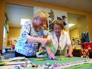 Lillian Elllison, a Village at Brookwood resident, shows another resident the art of quilting. The facility also offers needlework and sewing classes.