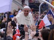Pope Francis gestures to a crowd from his vehicle.