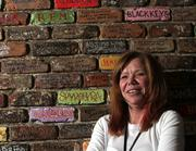 Karen Foley, Bogart's general manager, stands in front of a wall with the names of some of the bands that have played there. The club just underwent $100,000 in renovations.