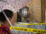 A pedestrian walks past the damaged facade of the United States Post Office in Napa.