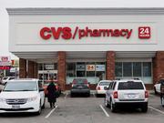Customers walk towards a CVS store.