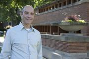 Geoffrey Baer poses in front of Frank Lloyd Wright's Chicago masterpiece the Robie House.