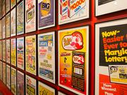 """One wall of the """"40 Years / 40 Stories"""" exhibit showcases historical advertisements from lottery ticket retailers."""
