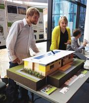 Matt Sedor (left) and Caty Head-Skogland show off the model of the SAGE team's green portable classroom.