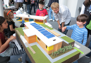 Architecture graduate student Matt Sedor (second from right) helps students as they take a gander at PSU's green portable classroom model at OMSI.  The showing was at the exhibit Planet Under Pressure, which dealt with climate change.