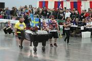 After loading three weighted kegs in a wheelbarrow, strongman competitors have to lift and move it.