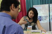 Kim Nishigaya, human resources consultant, talks to job fair-goers about available positions with Central Pacific Bank.
