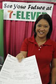 Grace Halsey, human resources specialist for 7-Eleven Hawaii, hands out job applications. 7-Eleven has openings in various store locations around Hawaii.