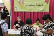 Jamba Juice Hawaii District Manager Mike Palmer, left, throws a shaka, while Training Manager Deann Aiu hands out job applications. Aiu says they are trying to staff existing stores and have close to 100 openings.